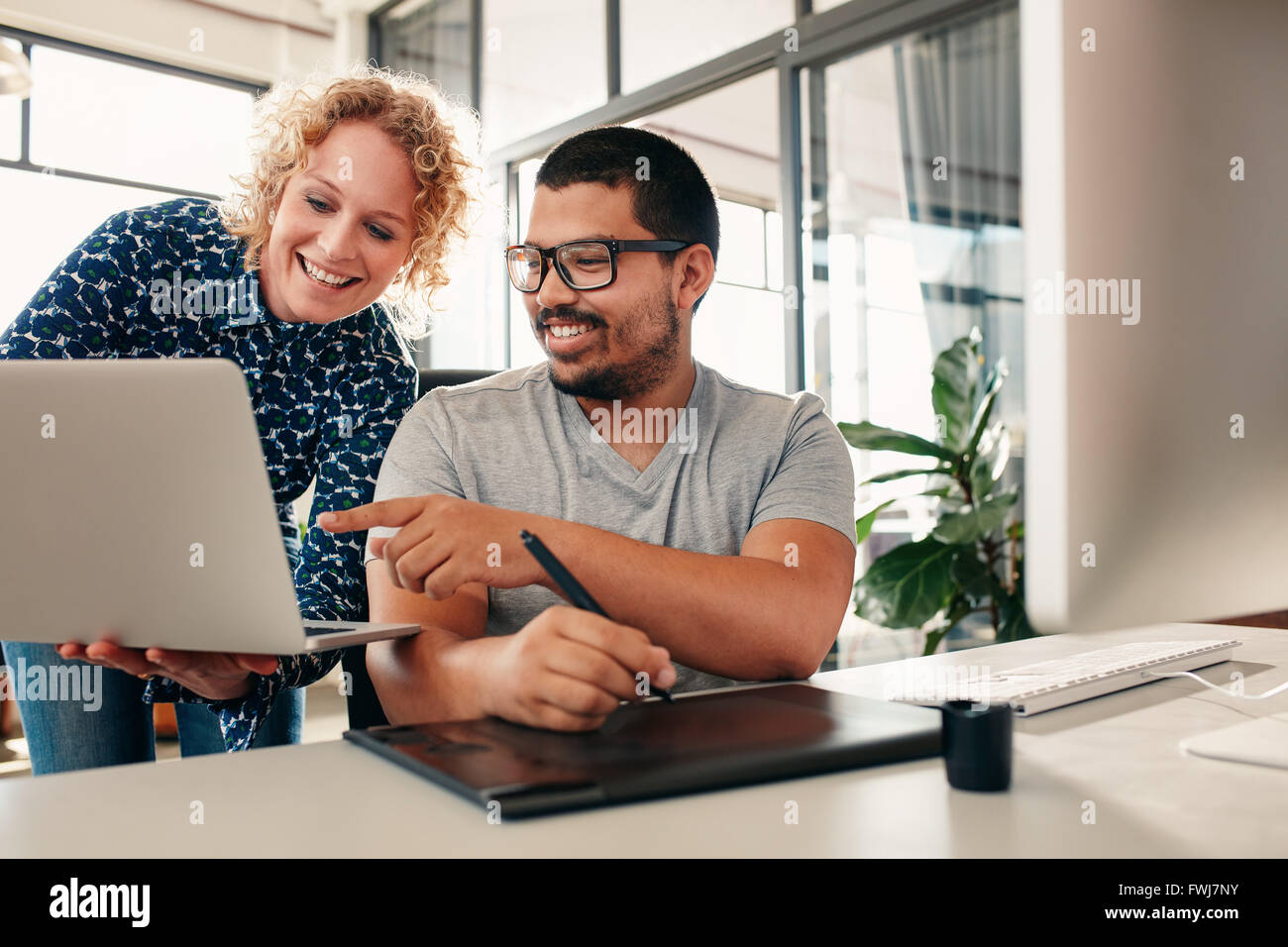 Two young graphic designers working together, with female colleague showing something man sitting at his des. Creative - Stock Image