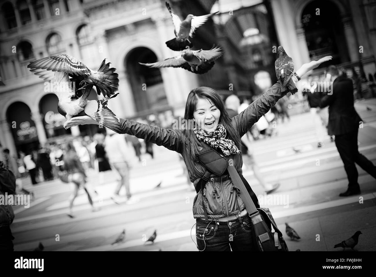 Beautiful and happy kazakh woman playing with doves - Stock Image