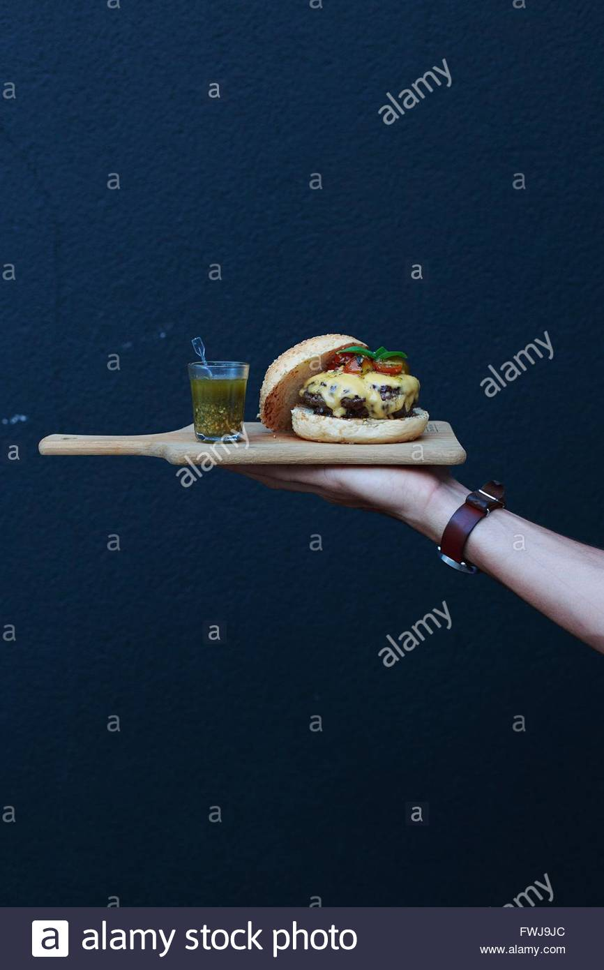 Cropped Hand Holding Burger And Drink On Cutting Board Against Wall - Stock Image