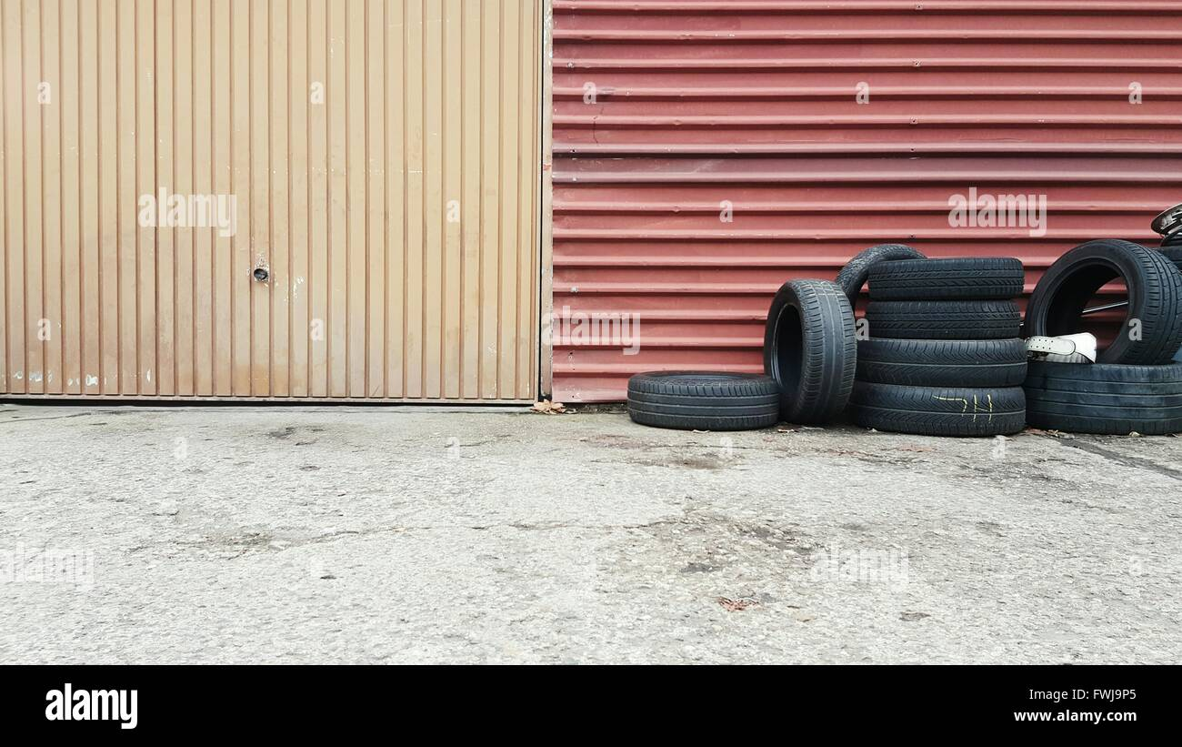 Tires Against Metallic Wall - Stock Image