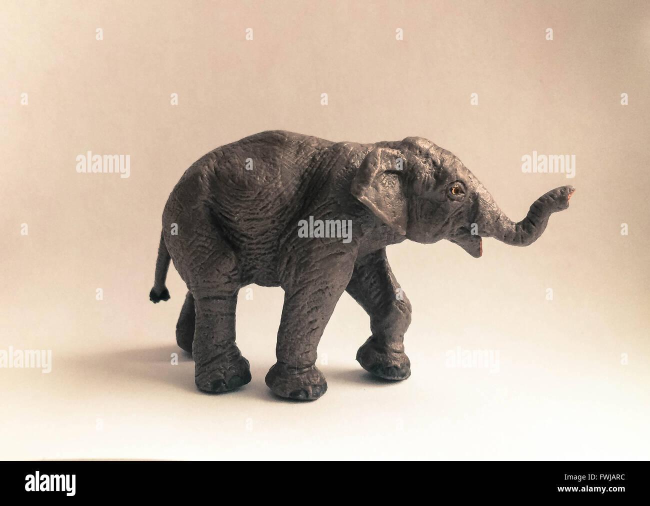 Close-Up Of Elephant Figurine On Beige Background - Stock Image