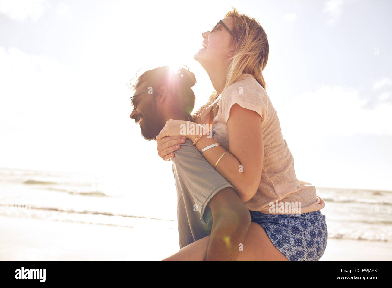 Side view portrait of young man carrying his girlfriend on his back at the beach. Man piggybacking girlfriend at - Stock Image