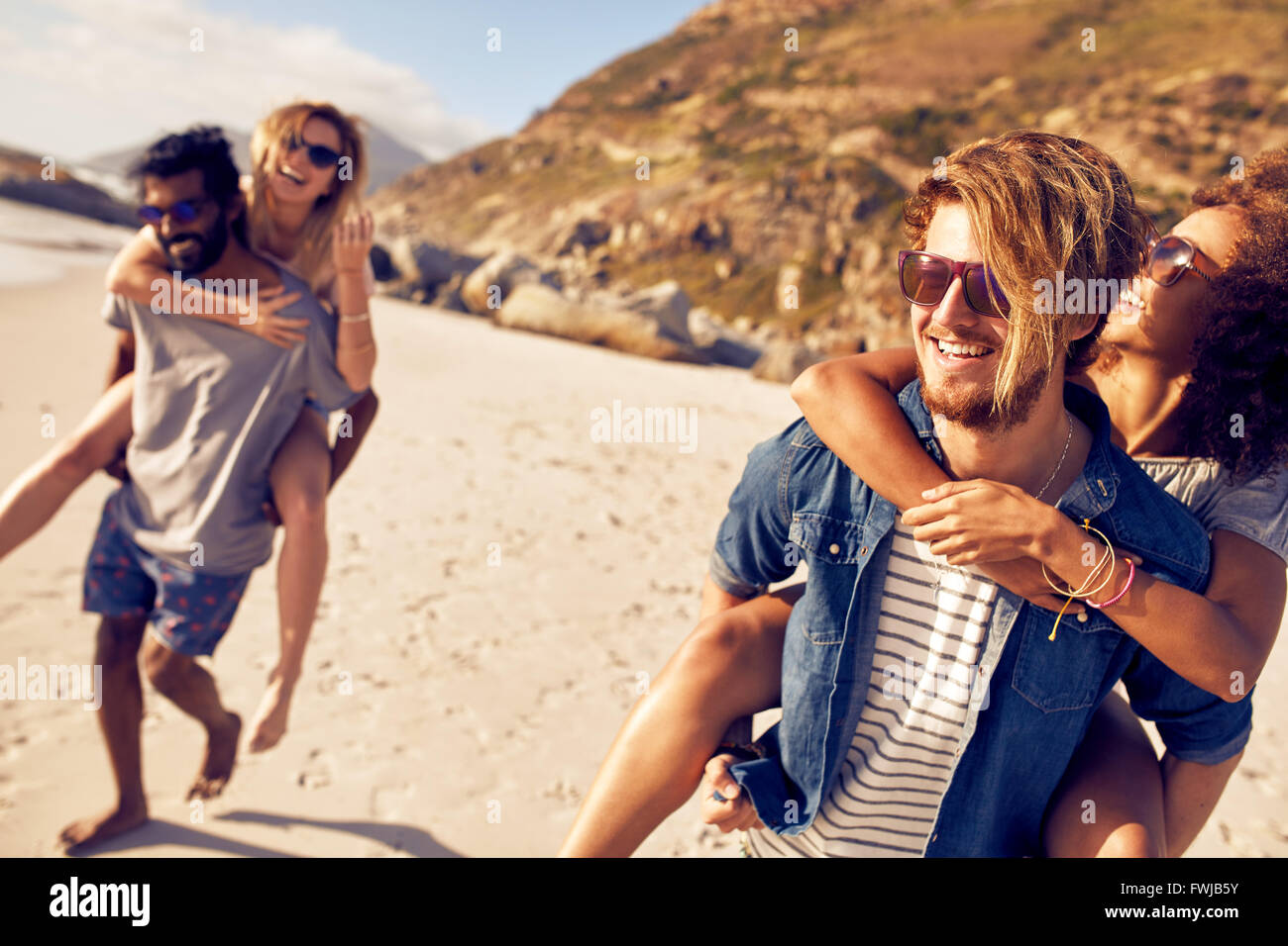 Young men piggybacking women on the sea shore. Mixed race young people enjoying summer vacation at beach. - Stock Image