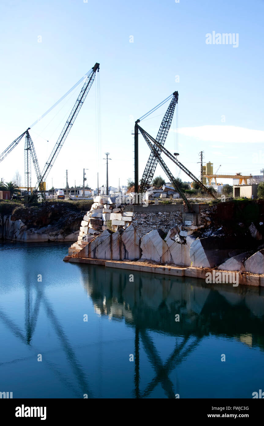 Cranes At Demolished Buildings By River Against Sky - Stock Image