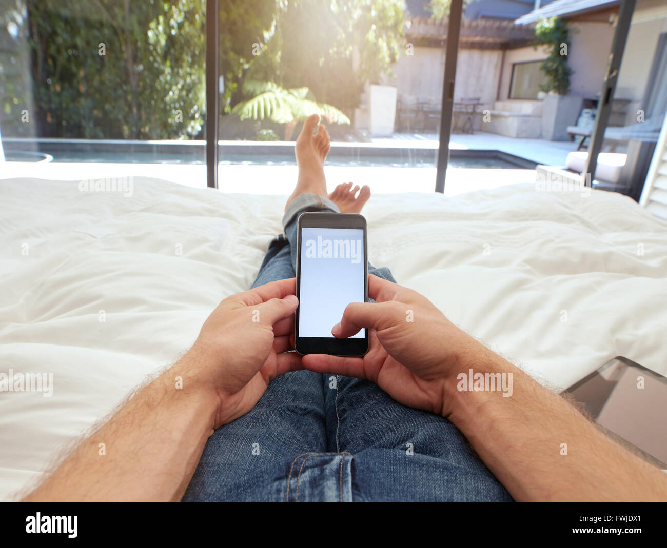 Closeup image of man lying on a bed holding a mobile phone with blank screen. POV shot of man relaxing in bedroom - Stock Image