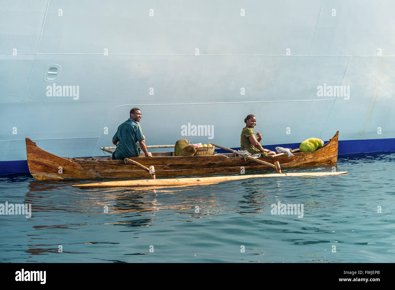 Malagasy vendors from their outrigger canoe offer crabs, fish and tropical fruits to - Stock Image