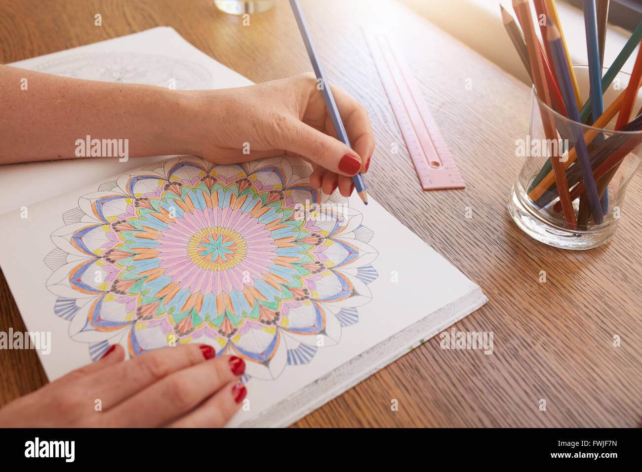 Close up image of woman hands drawing in adult colouring book on a table at home. - Stock Image