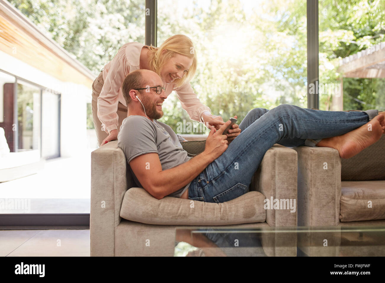 Indoor shot of mature couple at home using digital tablet and smiling. Man is sitting on sofa with woman standing - Stock Image