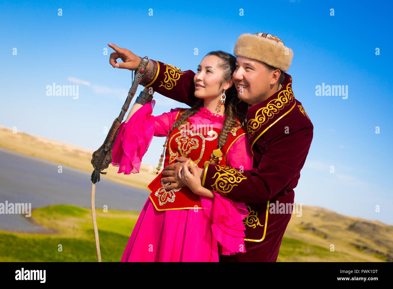 Man and woman together in the steppe in kazakh national costumes - Stock Image