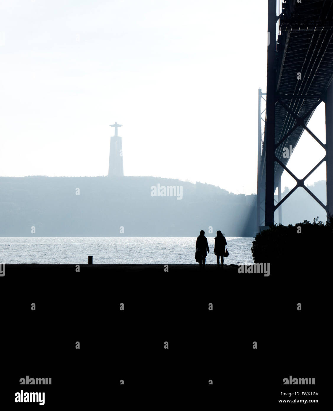 Friends Walking At Riverbank By April 25Th Bridge Against Christ The King Statue - Stock Image