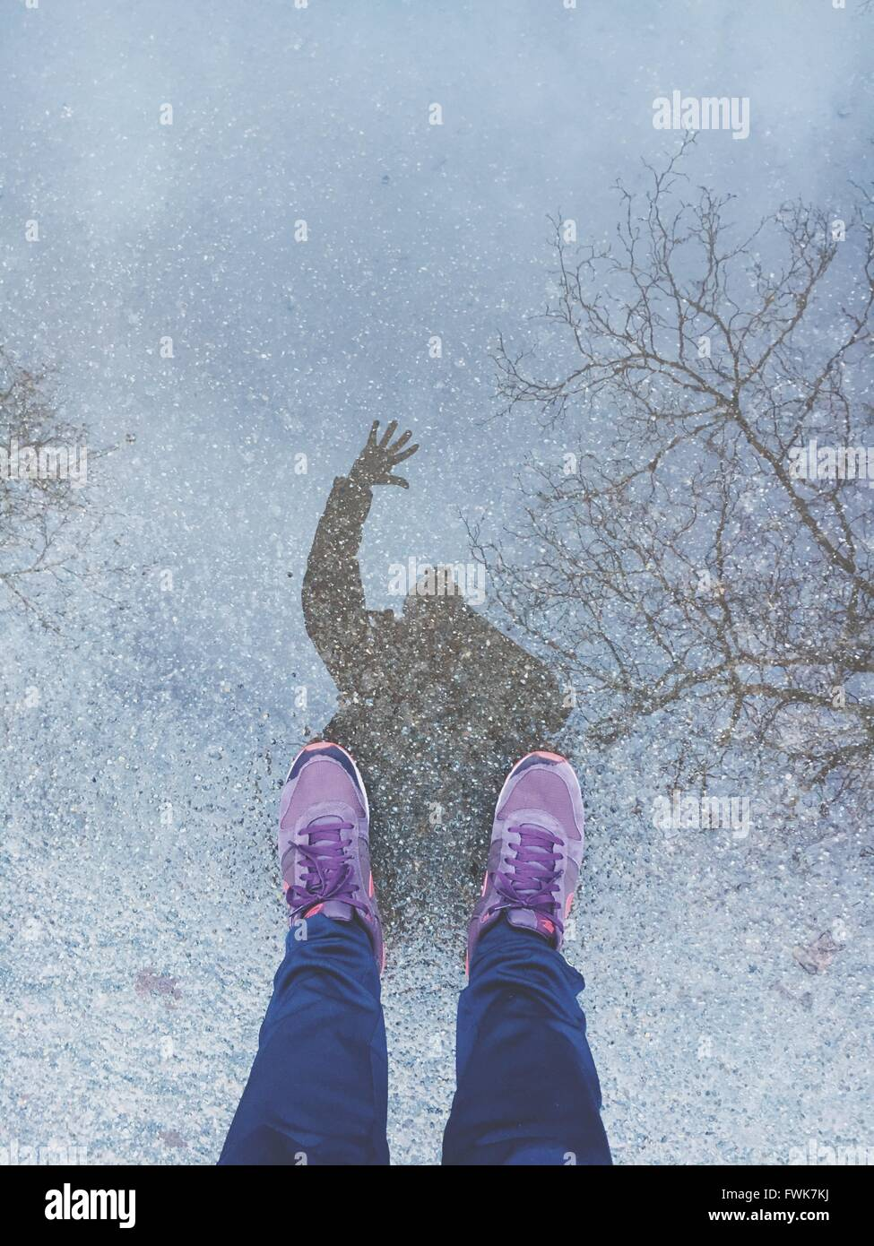 Low Section Of Woman Standing By Puddle - Stock Image