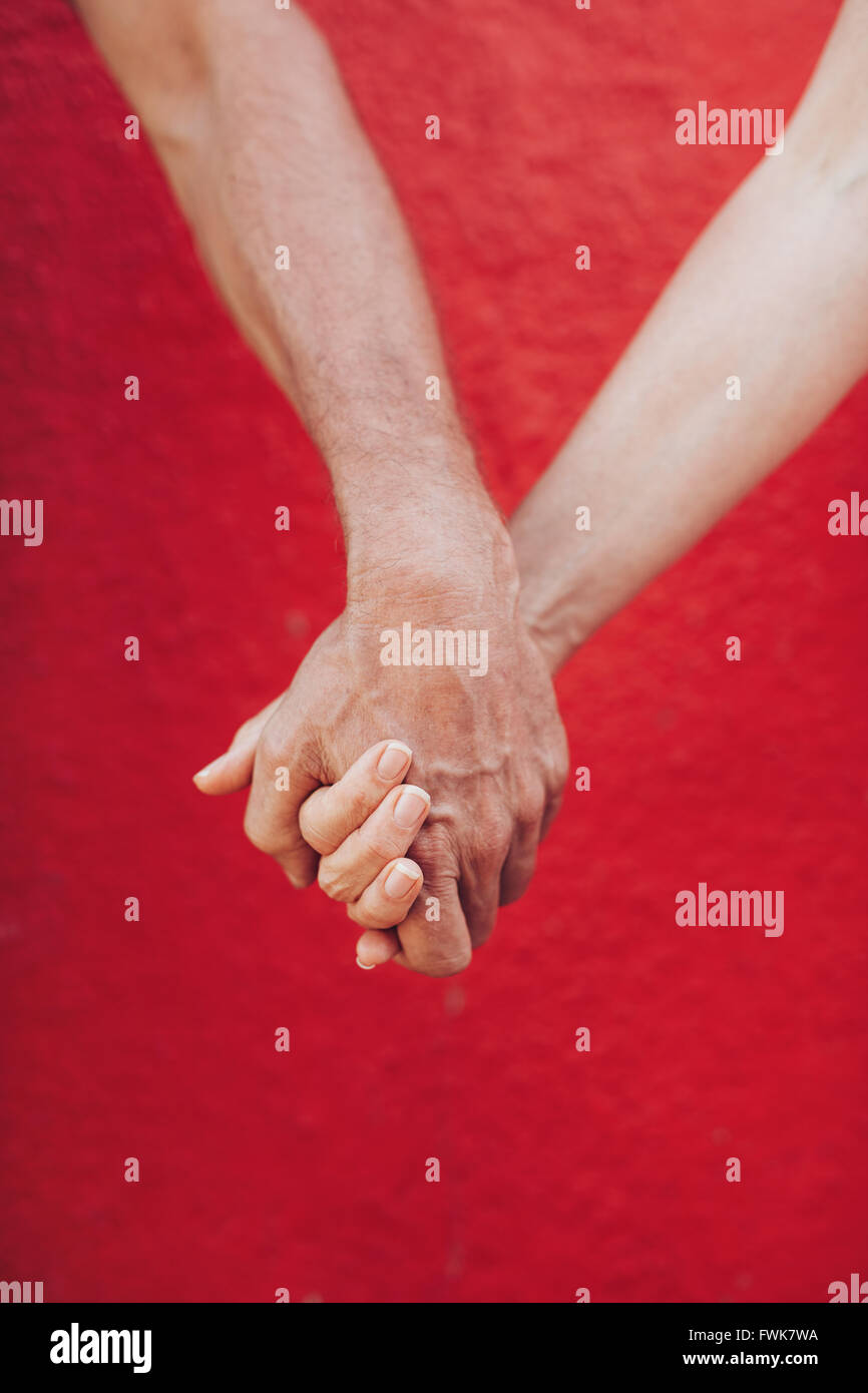 Close up of mature couple holding hands against red wall. Vertical shot of loving man and woman holding hands. - Stock Image