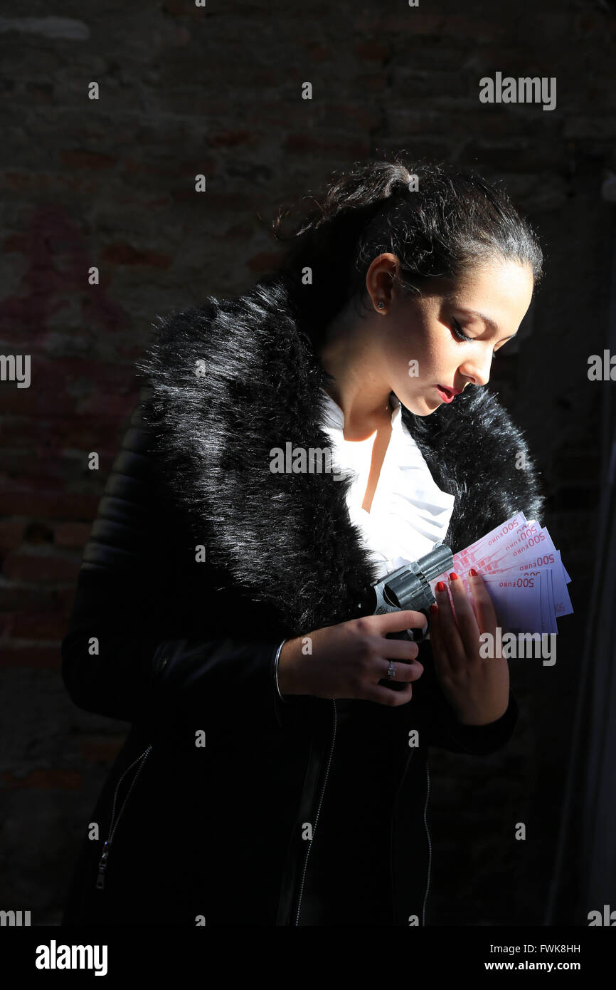 Gangster Holding Handgun And Currency Against Wall - Stock Image