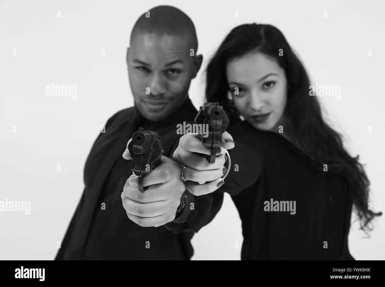 Portrait Of Fashionable Gangster Friends Aiming Gun At Camera Against White Background - Stock Image