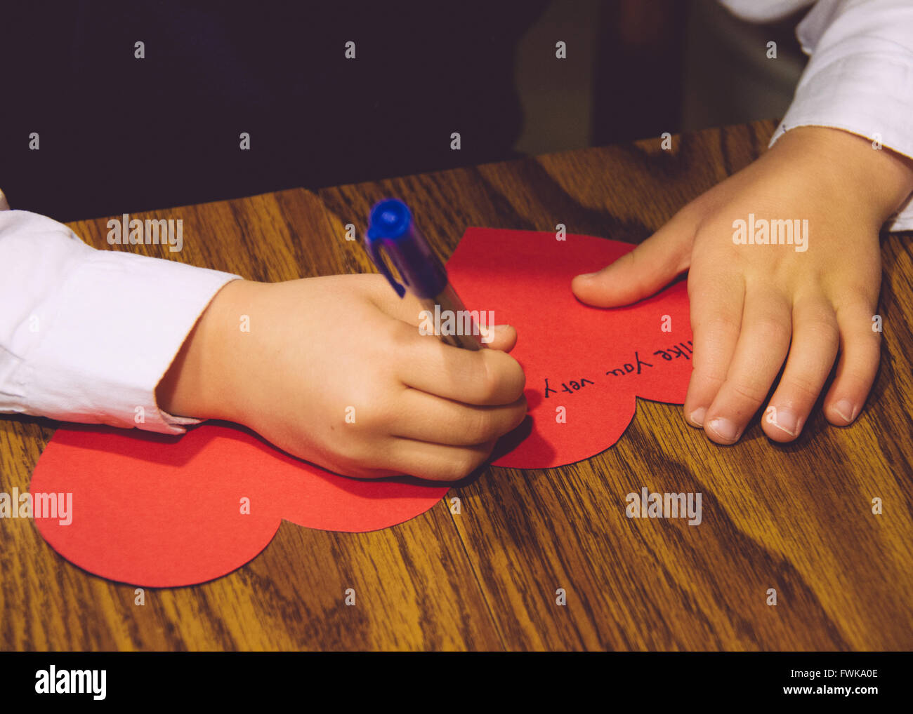 Cropped Image Of Child Writing On Heart Shape Greeting Card On Table - Stock Image