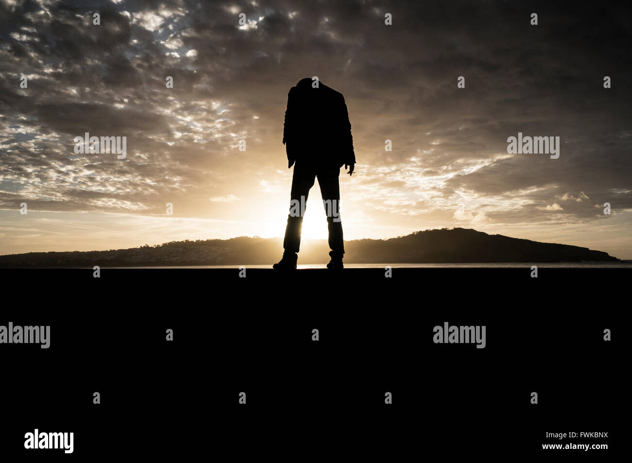 Silhouette Person Standing On Field Against Sky During Sunset - Stock Image