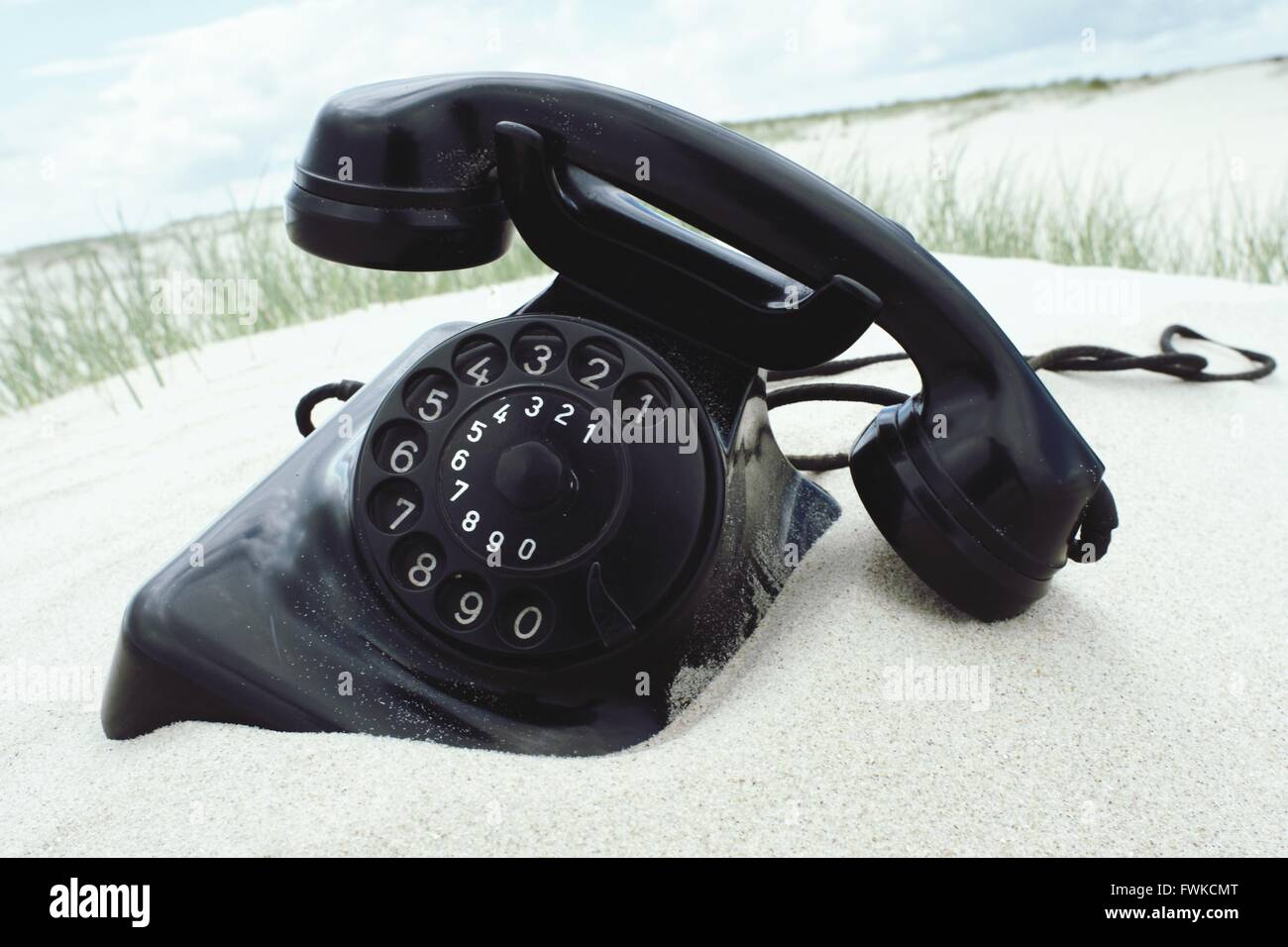Close-Up Of Retro Telephone On Sand - Stock Image