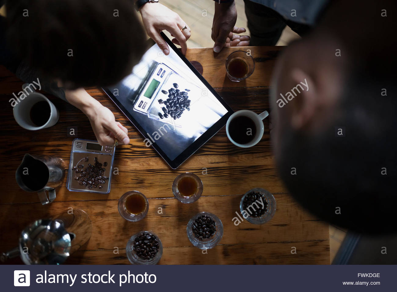 Overhead entrepreneurial coffee roasters using digital tablet - Stock Image