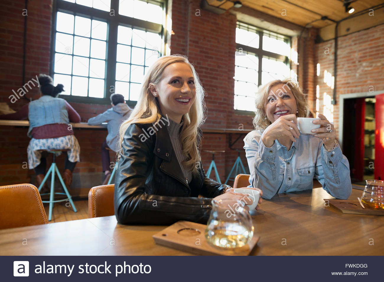 Smiling mother and daughter drinking tea in coffee shop - Stock Image
