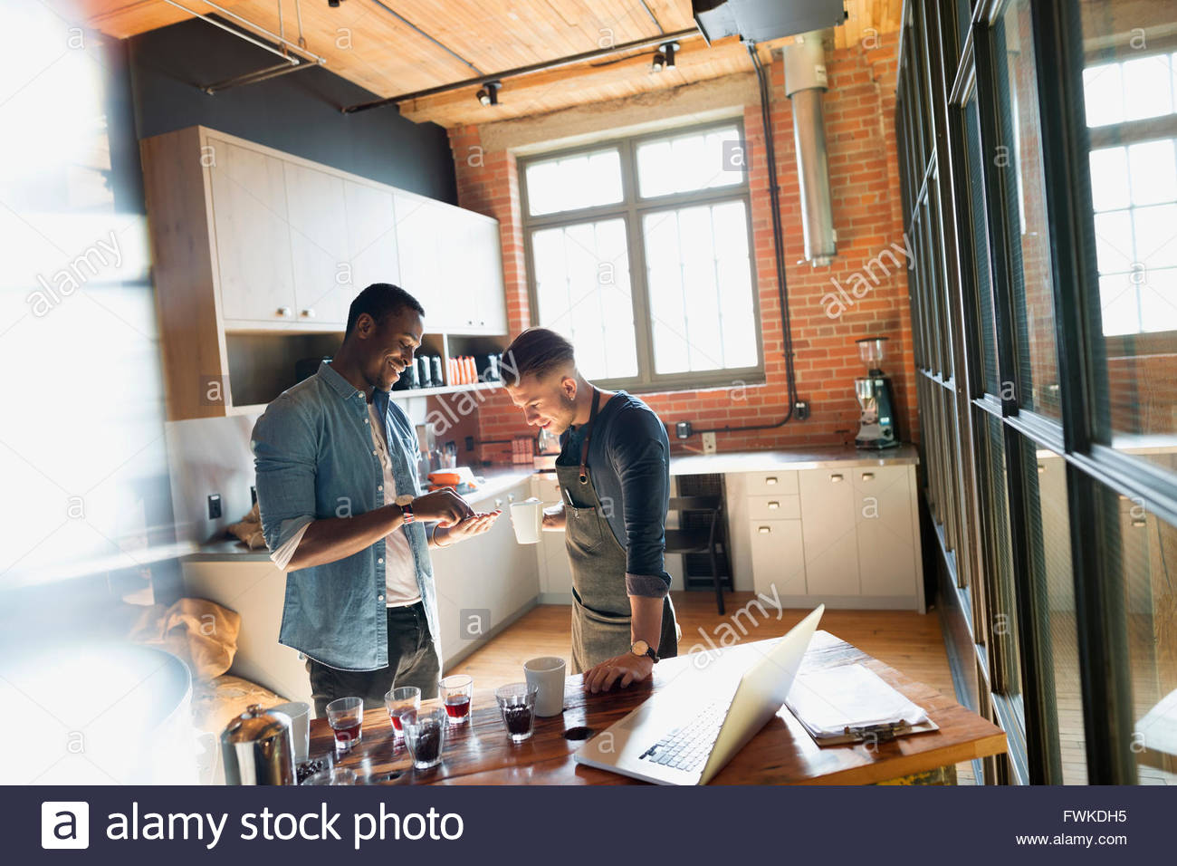 Entrepreneurial coffee roasters examining coffee beans in kitchen - Stock Image