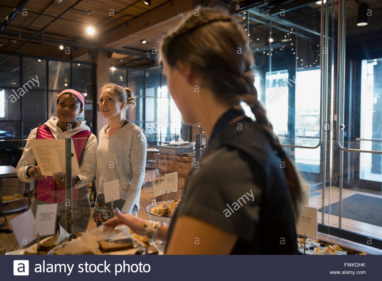 Bakery worker waiting for customers to order - Stock Image