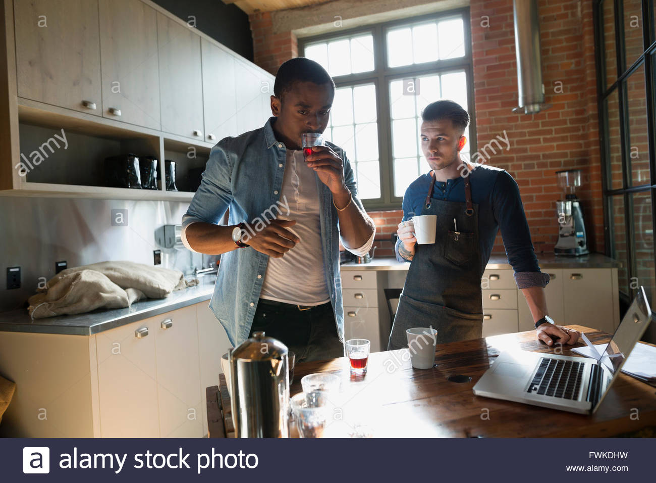 Entrepreneurial coffee roaster smelling coffee in kitchen - Stock Image
