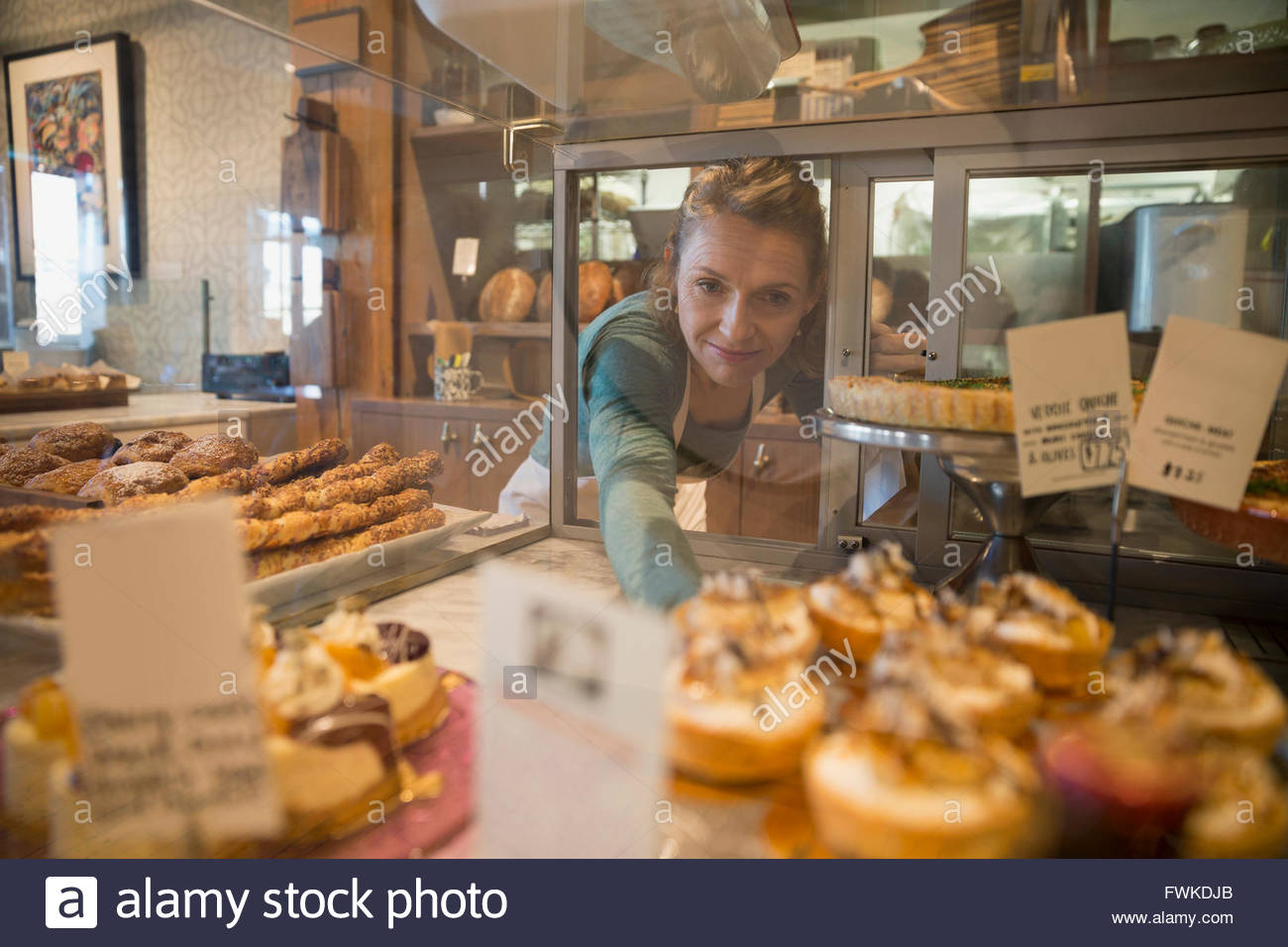 Bakery owner reaching for pastries in display case - Stock Image