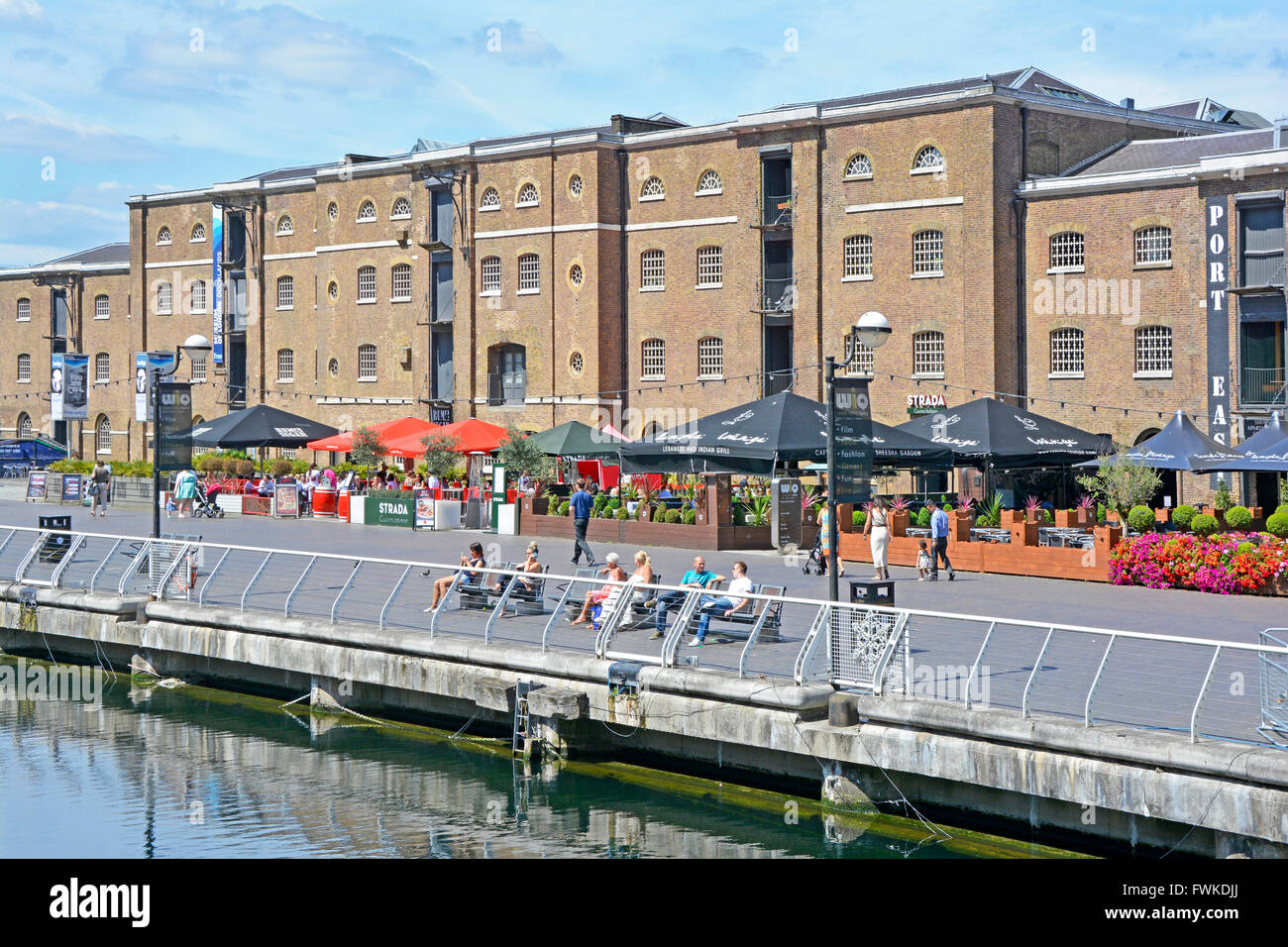 Outdoor restaurant & converted warehouses beside North Dock of old West India Docks at Canary Wharf London Docklands, - Stock Image