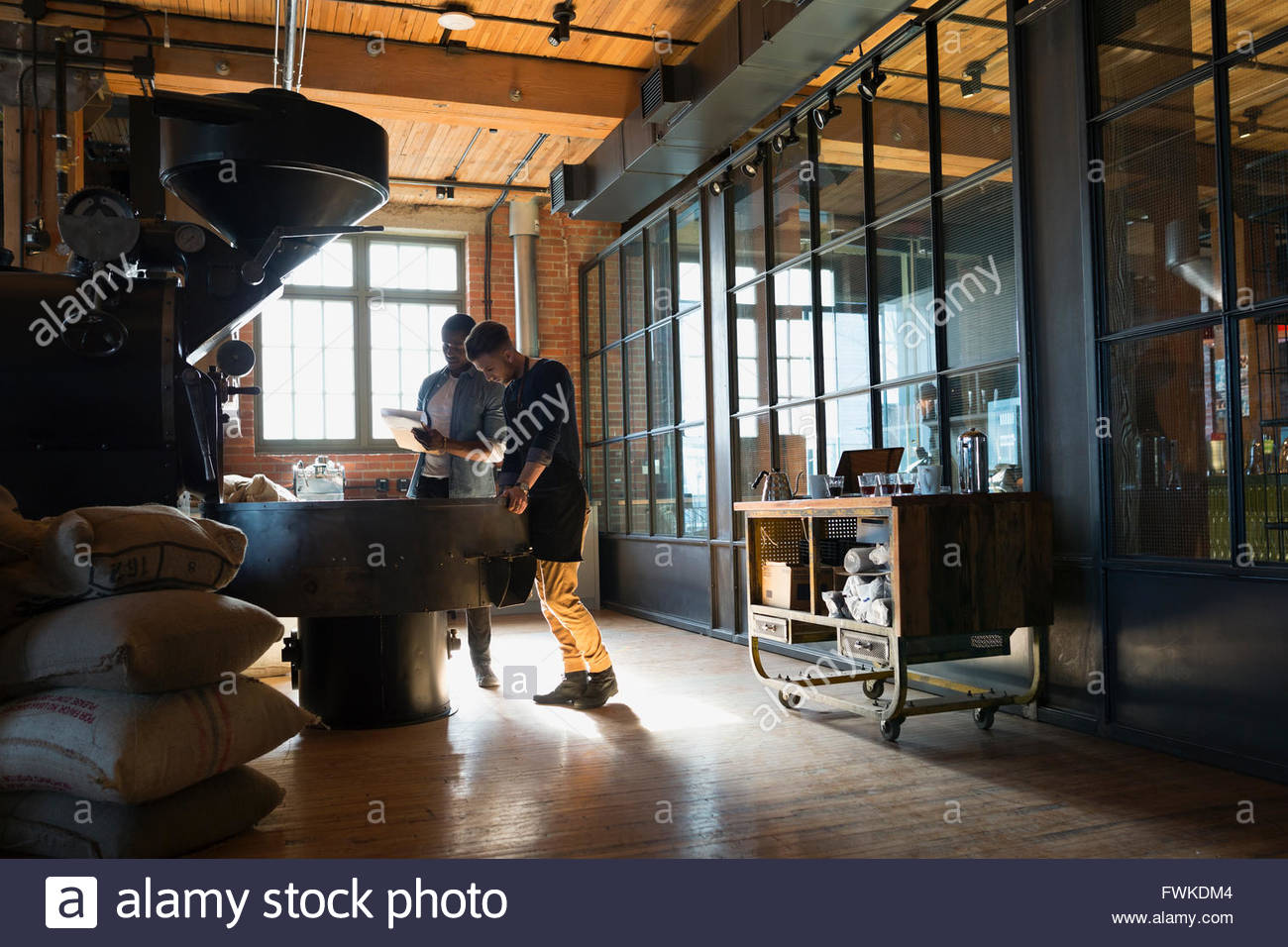 Coffee roasters working at coffee roasting machine - Stock Image
