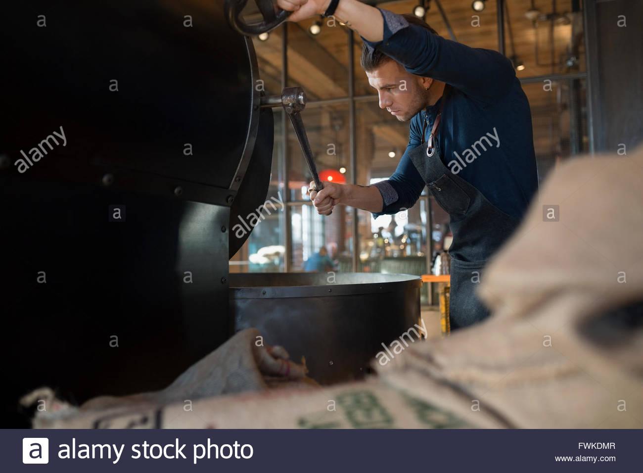 Coffee roaster using coffee roasting machine - Stock Image