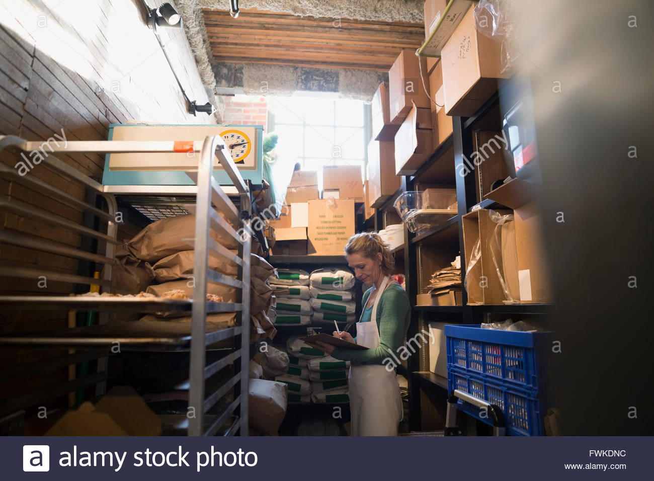 Bakery owner checking supplies inventory in storage room - Stock Image