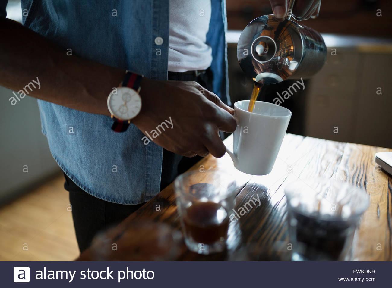 Entrepreneurial coffee roaster pouring coffee into mug - Stock Image