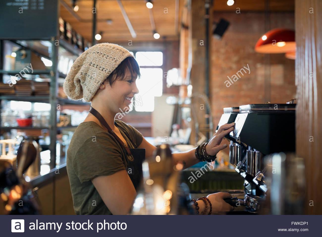 Barista using espresso machine in coffee shop - Stock Image