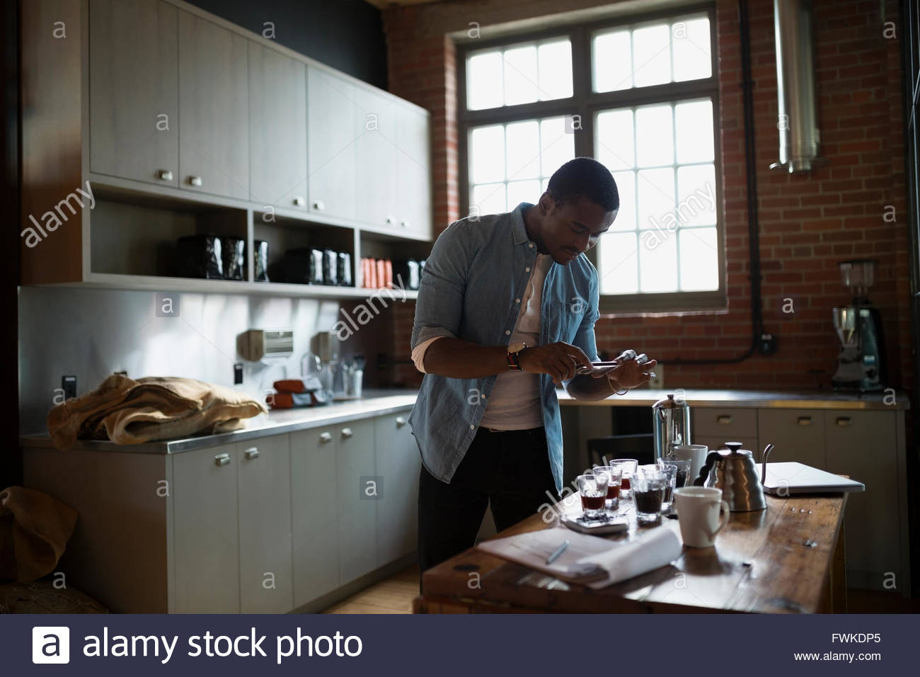 Entrepreneurial coffee roaster photographing coffee in kitchen - Stock Image