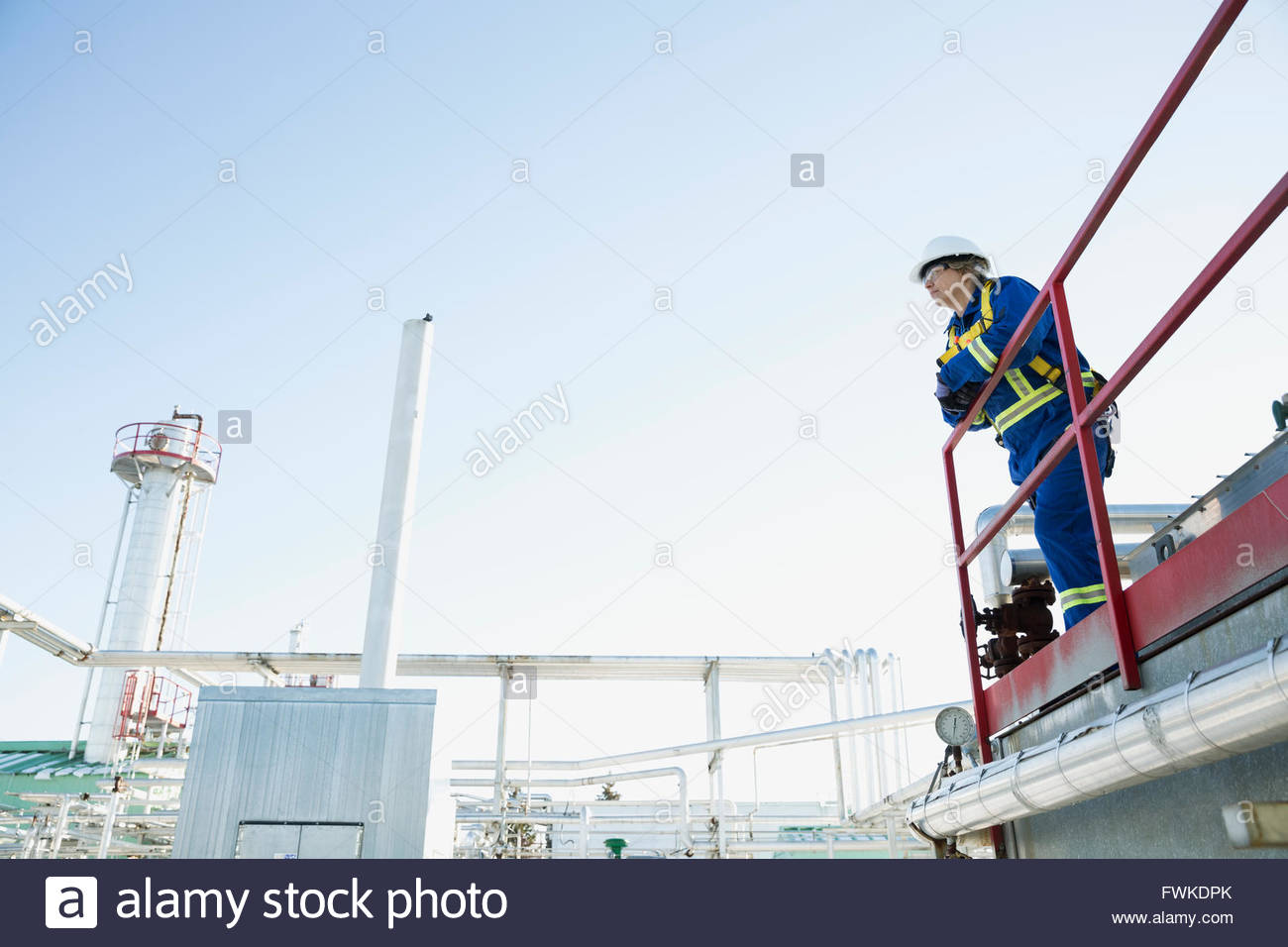 Female worker on platform overlooking gas plant - Stock Image