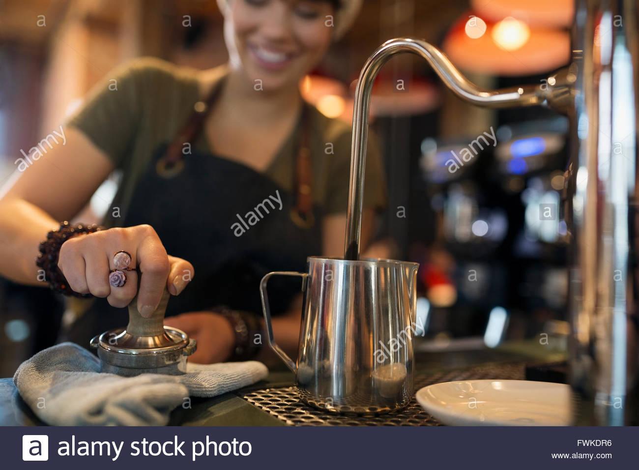 Barista pressing espresso with tamper in coffee shop - Stock Image