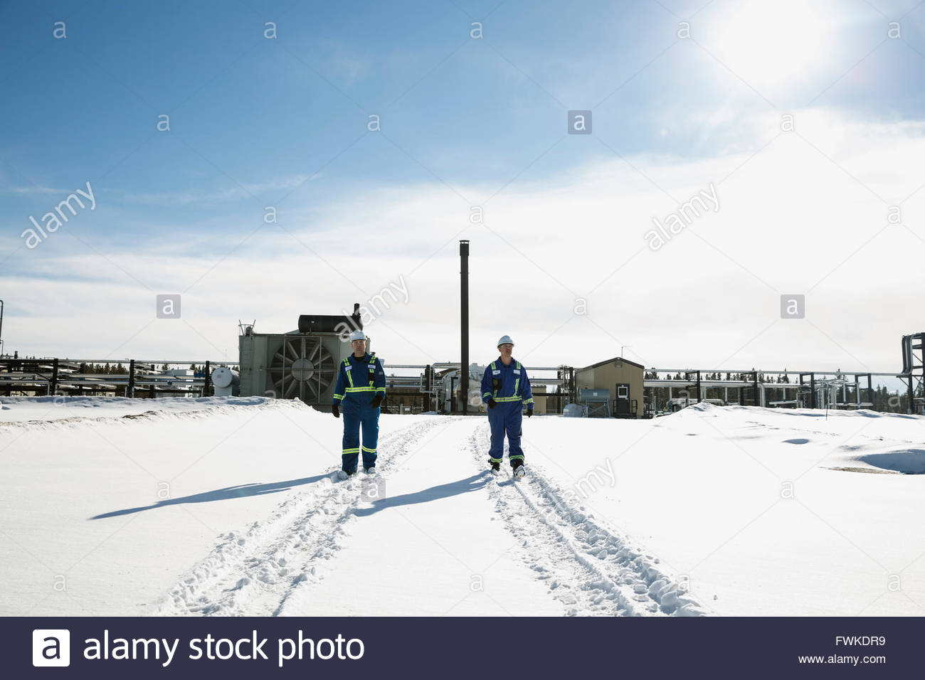 Workers walking in snow away from gas plant - Stock Image