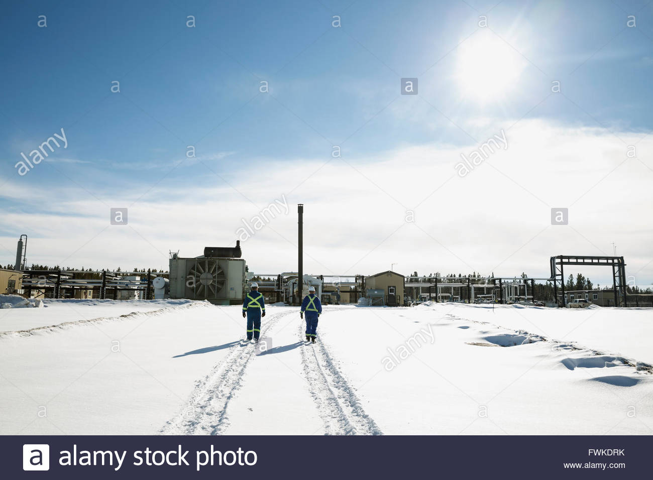 Workers walking in snow toward gas plant - Stock Image
