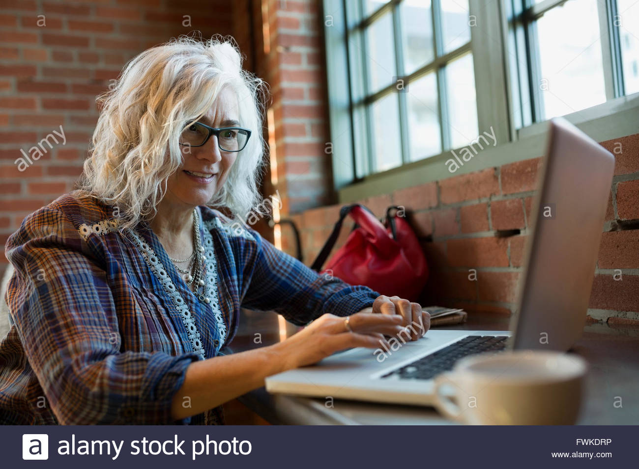 Woman working on laptop in coffee shop Stock Photo