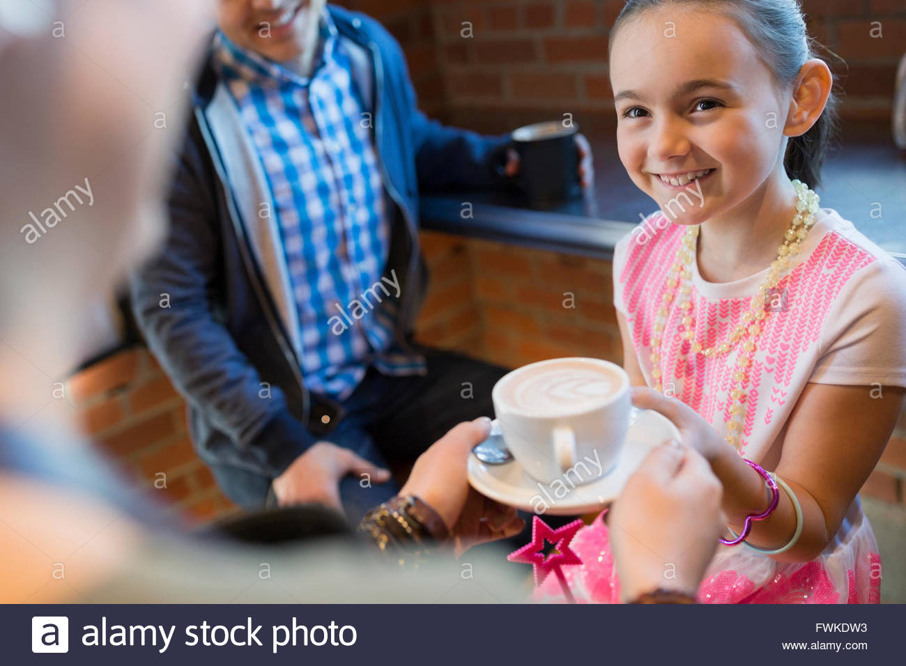Barista serving cappuccino to girl in coffee shop - Stock Image