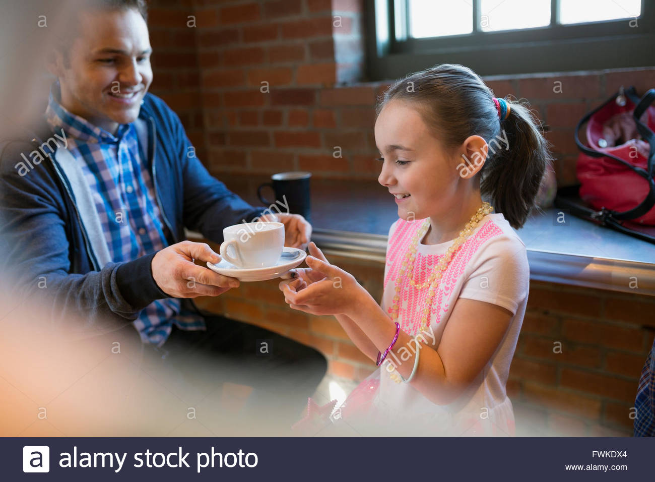 Father and daughter with cappuccino in coffee shop - Stock Image