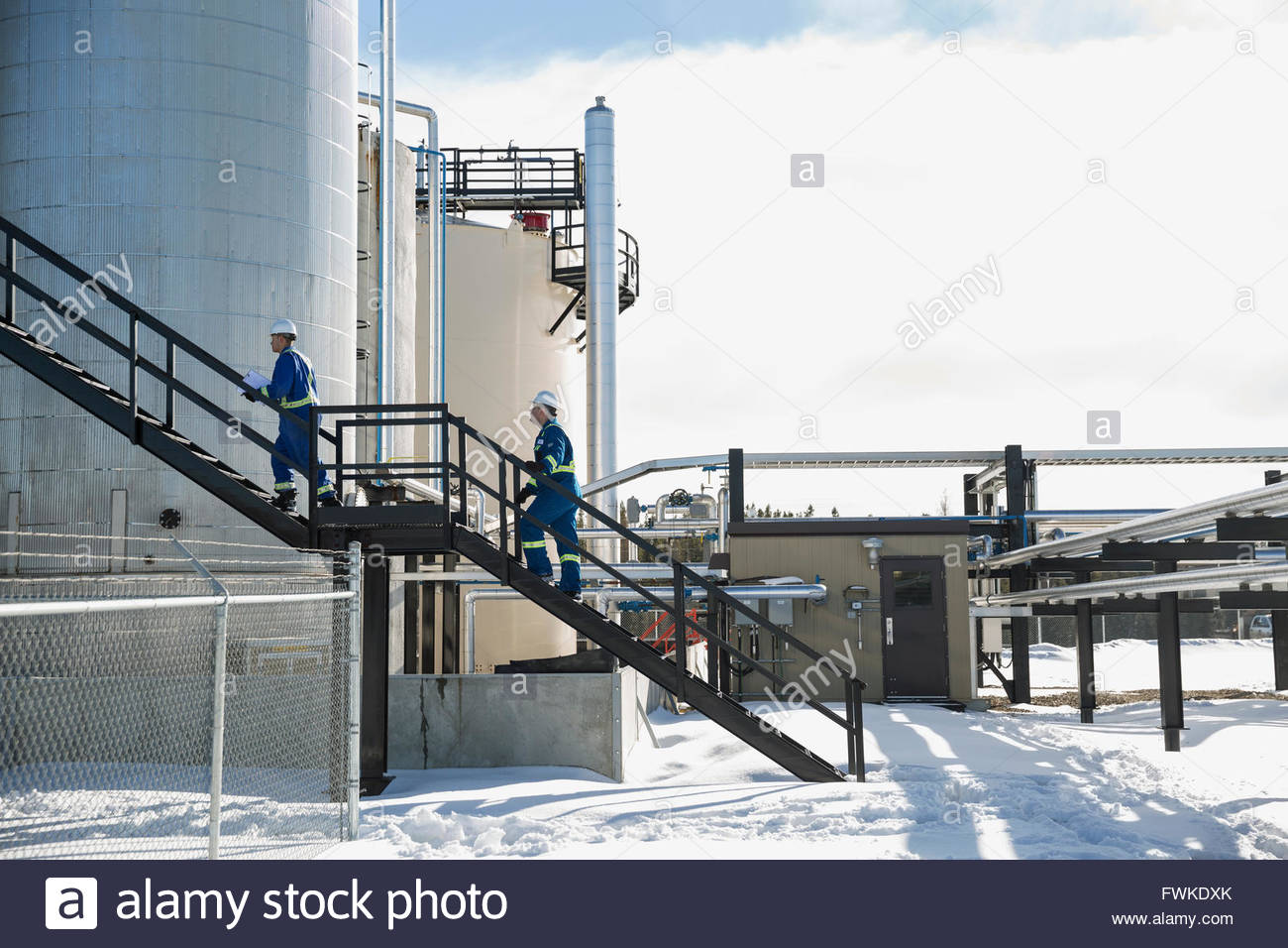 Workers ascending stairs at gas plant - Stock Image