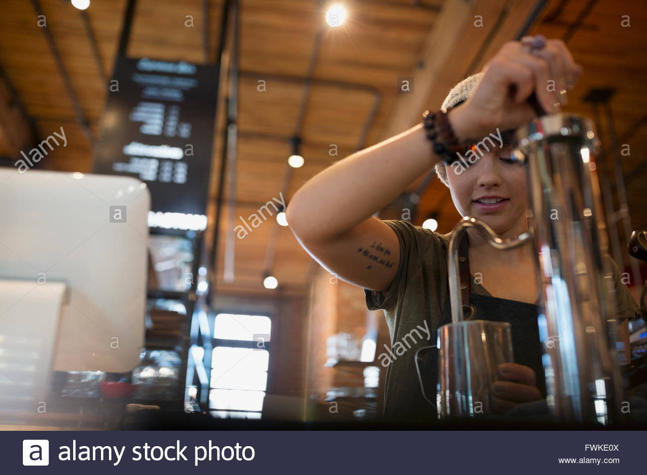 Barista foaming milk in coffee shop - Stock Image