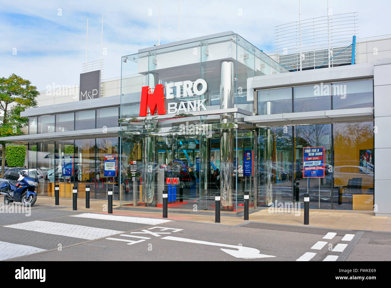 Metro bank branch premises & sign logo in town centre retail park development with large adjacent car park in - Stock Image