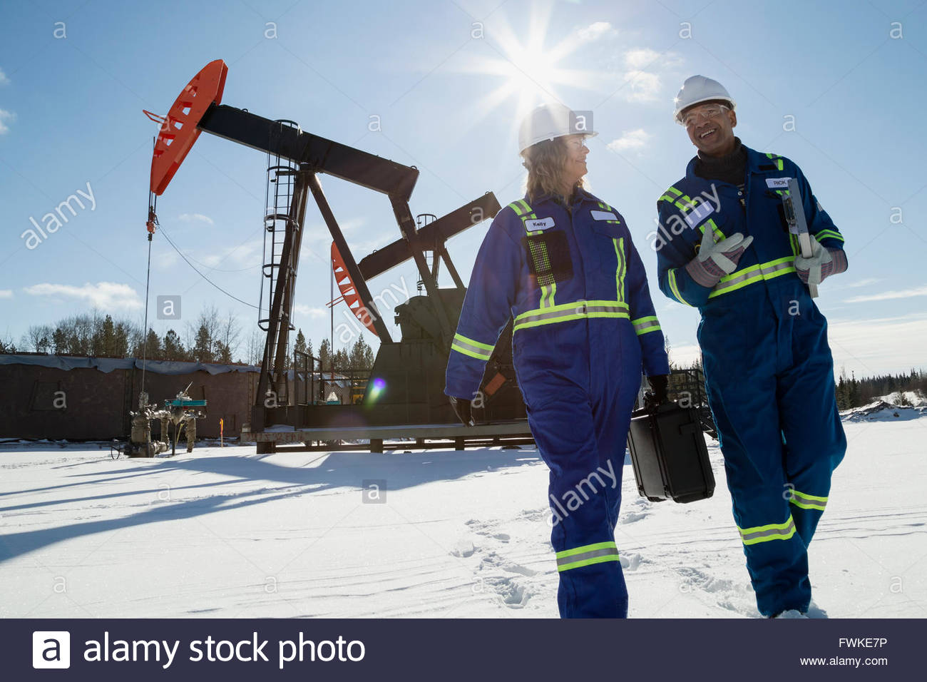 Workers walking away from drilling rigs in snow - Stock Image