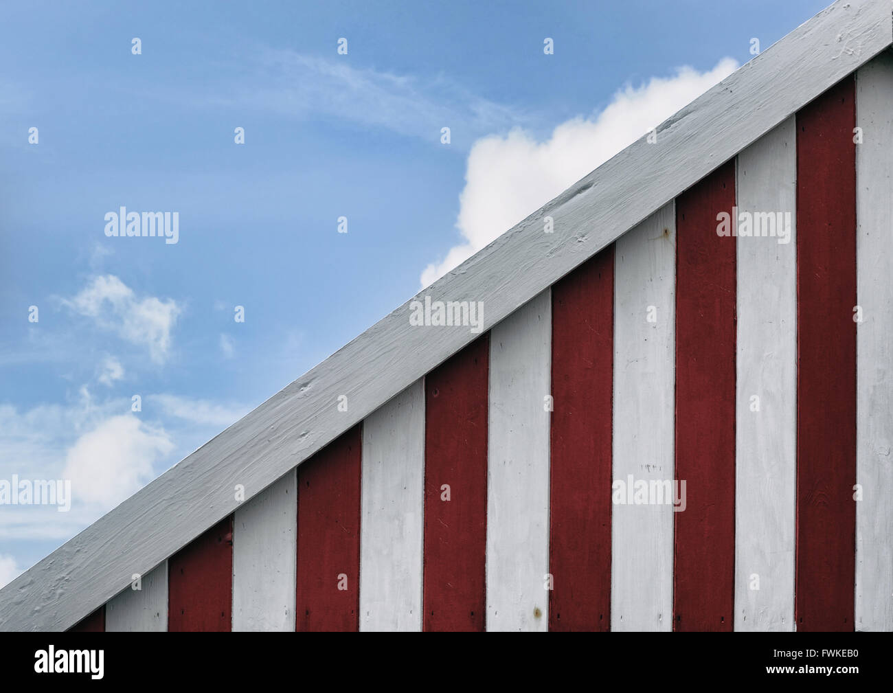 Beach hut abstract in the UK. Red and white stripes against a blue sky - Stock Image
