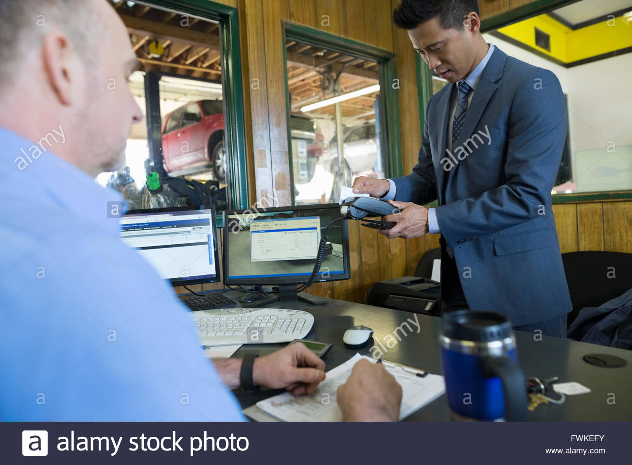 Customer using credit card reader auto shop office - Stock Image