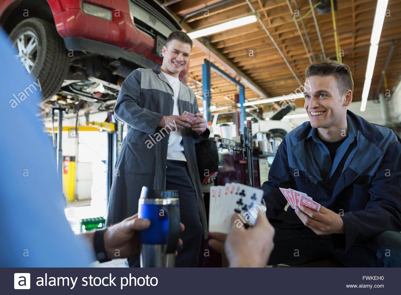 Mechanics playing cards in auto repair shop - Stock Image