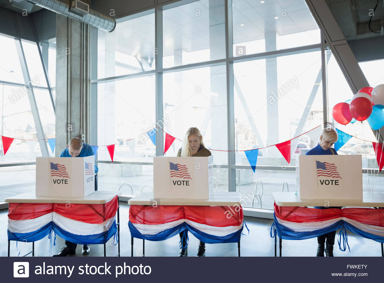 People in voting booths at polling place - Stock Image