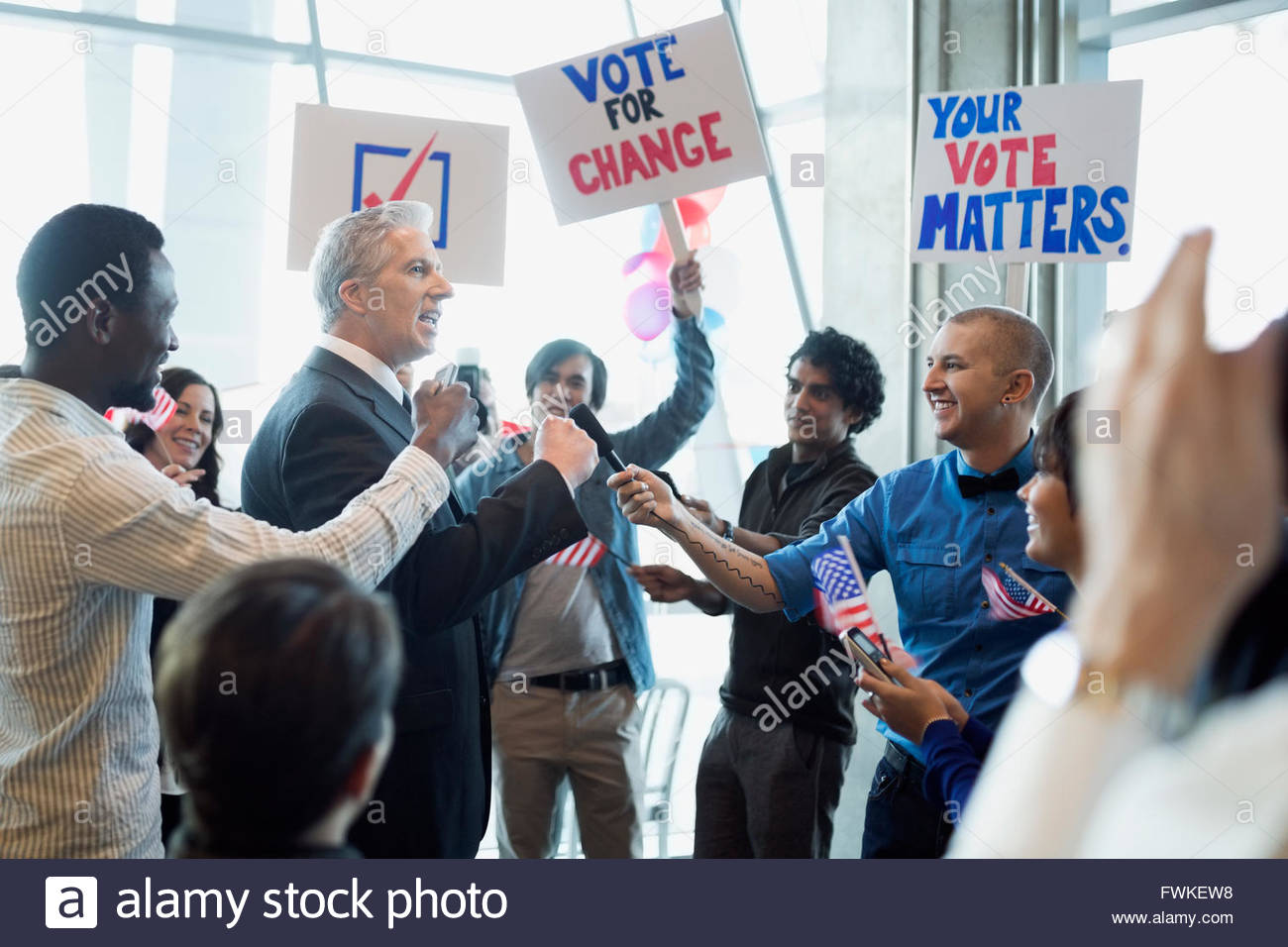 Politician greeting voters with signs at political rally - Stock Image